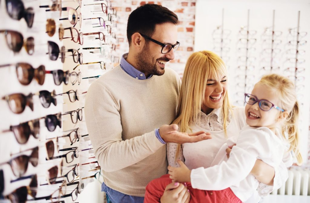 Parents helping girl choose glasses at optometrist office